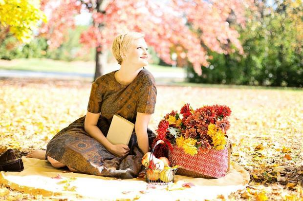 красивая девушка сидит на земле с корзиной осенних цветов