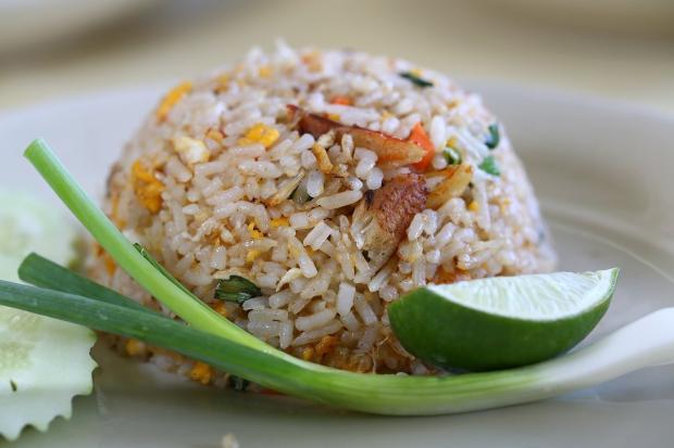 на тарелке лежит жареный рис горкой