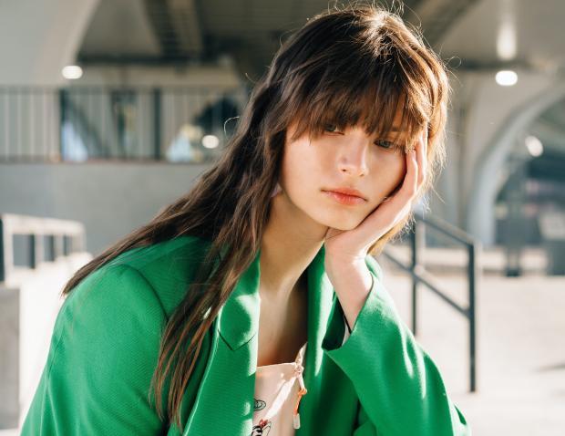 длинноволосая брюнетка в зеленом пиджаке