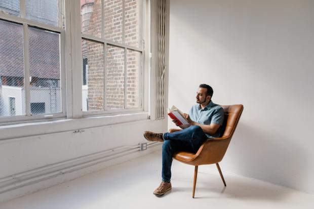 мужчина в рубашке и брюках сидит в кресле