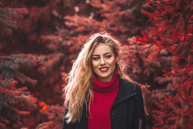 девушка в красном свитере улыбается на осенней аллее