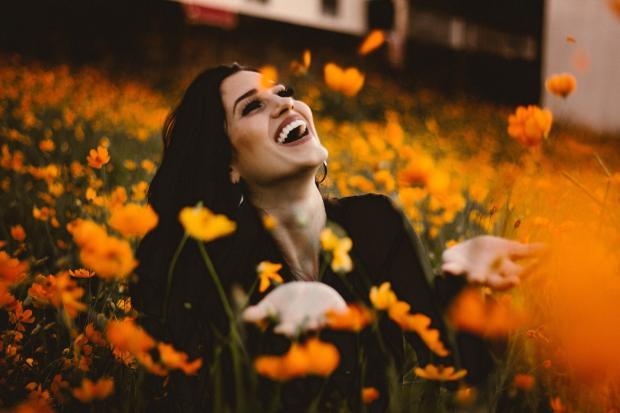 брюнетка смеется среди оранжевых цветов