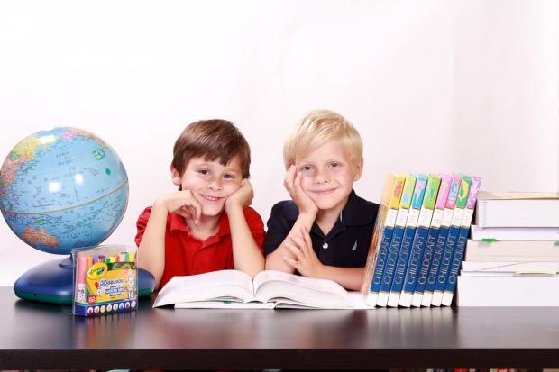 два мальчика сидят за столом с книгами и глобусом