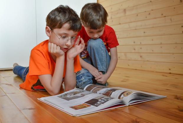 два мальчика в оранжевых футболках рассматривают иллюстрации в книге