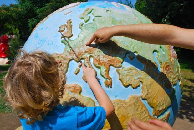 ребенок изучает большой глобус Земли