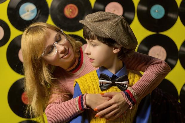 мама обнимает сына в кепке
