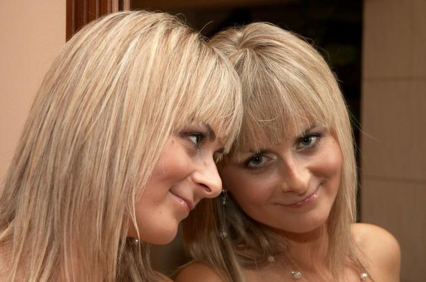 красивая блондинка стоит у зеркала