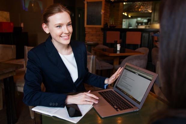 девушка в офисе работает за ноутбуком