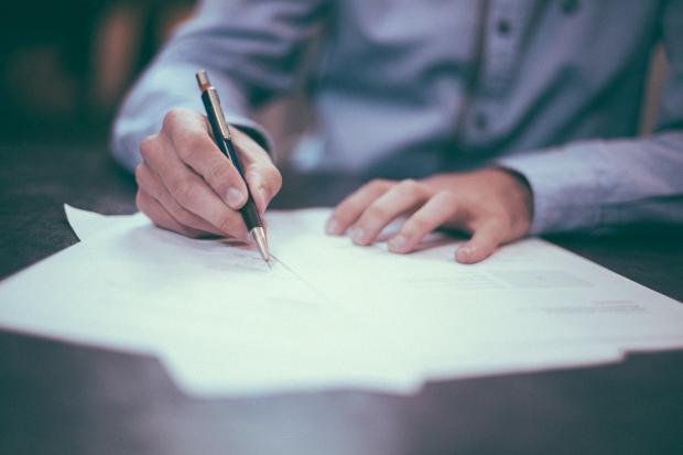 мужчина пишет ручкой на бумаге