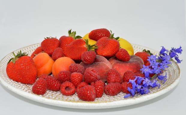 на белой тарелке насыпаны клубника и малина
