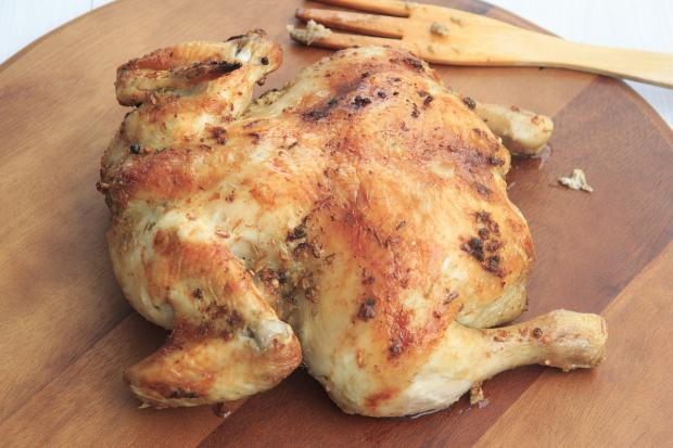 зажаренная курица лежит на деревянной  доске
