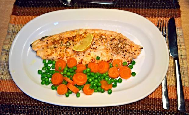 на продолговатой белой тарелке приготовлена запеченная рыба с овощами