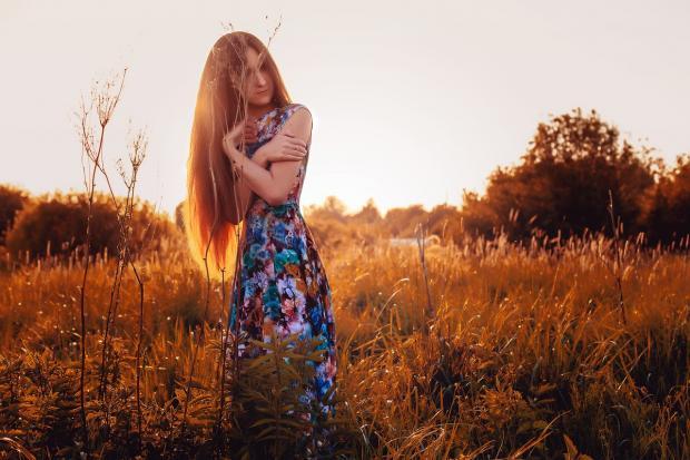 стройная длинноволосая девушка в цветастом платье стоит в поле на закате