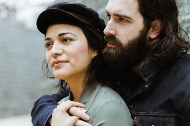 бородатый мужчина обнимает девушку в кепке