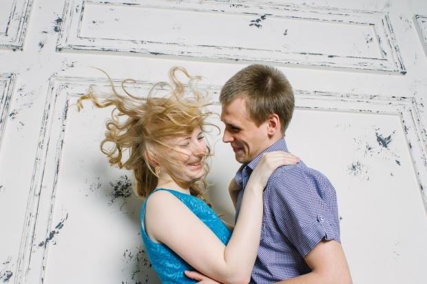 мужчина обнимает девушку с развевающимися волосам