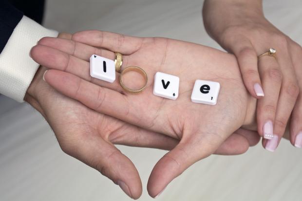 на ладони лежит обручальное кольцо и выложено слово Любовь