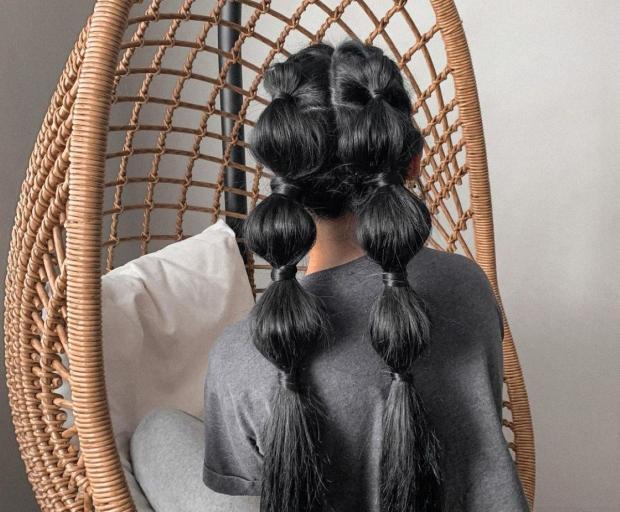 брюнетка с двумя пузырчатыми косами сидит в гамаке