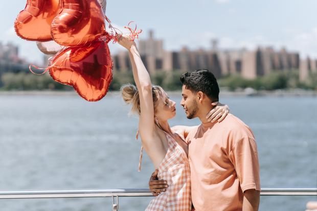 парень обнимает девушку с воздушными шариками в виде сердец