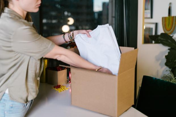 девушка кладет документы в коробку