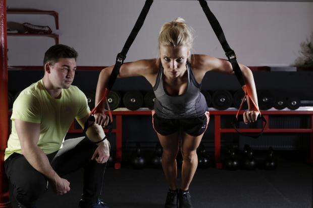 девушка в спортзале с инструктором
