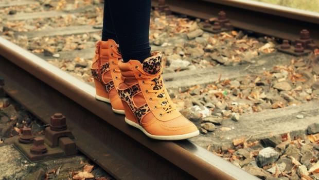 женские ноги в ботинках стоят на рельсах