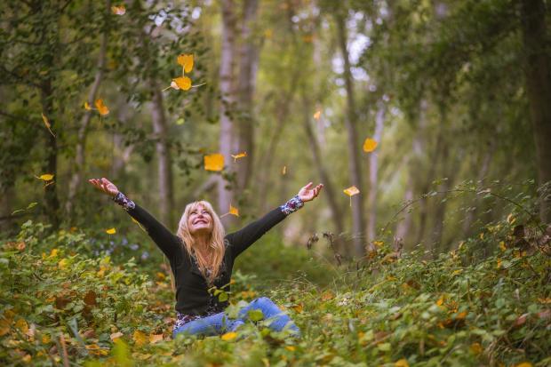 женщина подбрасывает осенние листья вверх в лесу