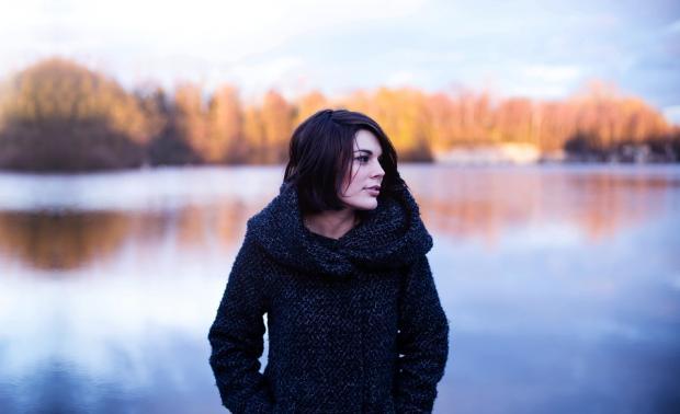 женщина стоит на берегу осеннего озера