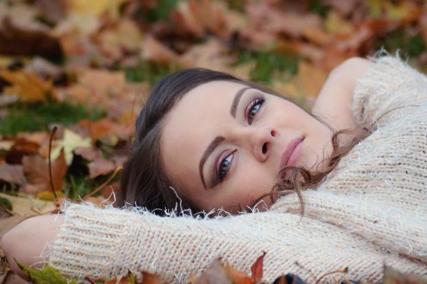 девушки в белом свитере лежит на осенней листве