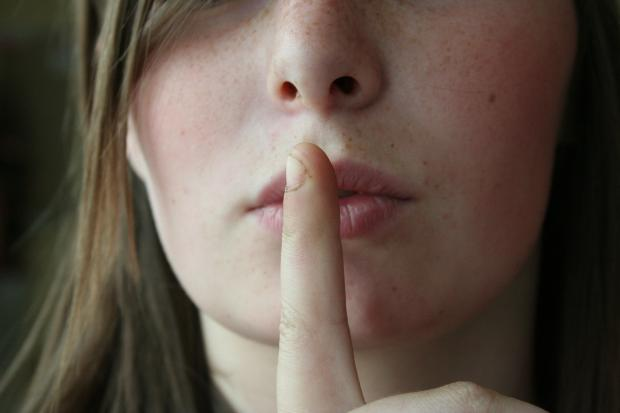 женское лицо, палец у рта