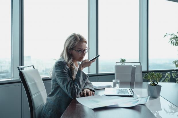 девушка в офисе перед компьтером, в руке телефон