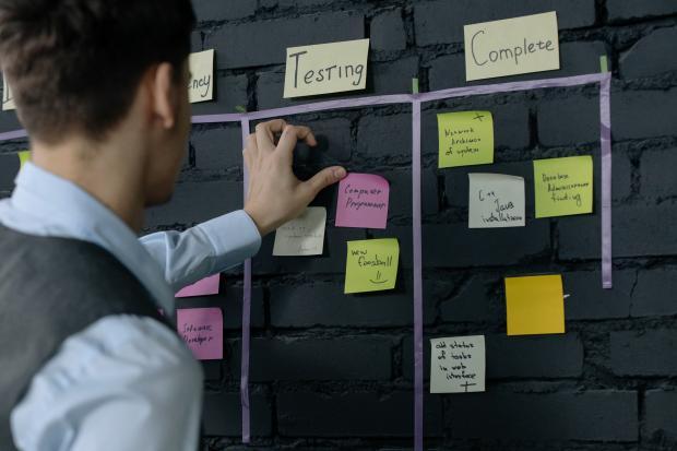 мужчина расклеивает на серой стене яркие бумажки