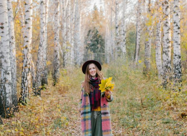 девушка с букетом из желтых листьев в осеннем лесу