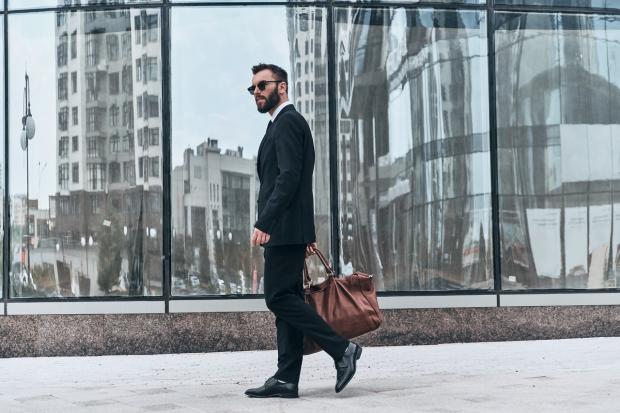 мужчина с сумкой идет по городу