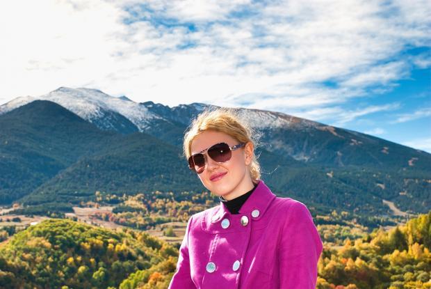девушка в солнцезащитных очках улыбается на фоне гор