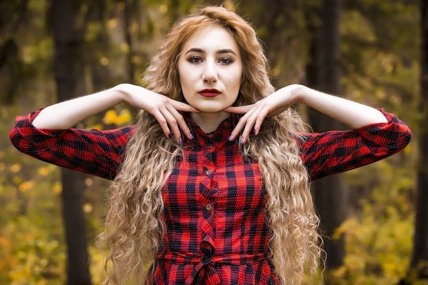 блондинка с длинными кудрявыми волосами в красной клетчатой рубашке стоит в осеннем лесу