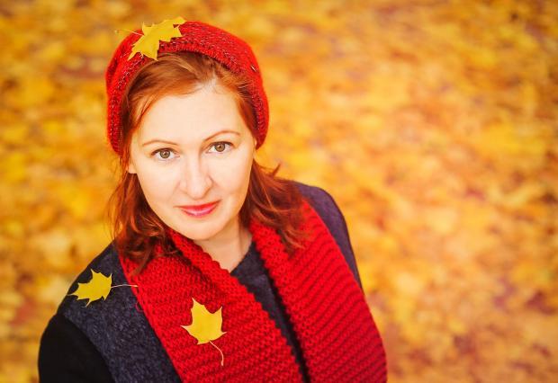 девушка стоит на осенней аллее в красной шапочке и шарфике в листьях