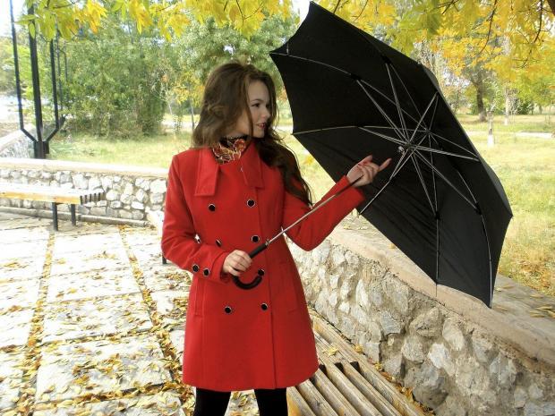 девушка в красном пальто закрывает черный зонт