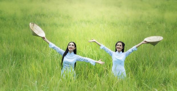 две девушки в белых  платья посреди зеленого поля