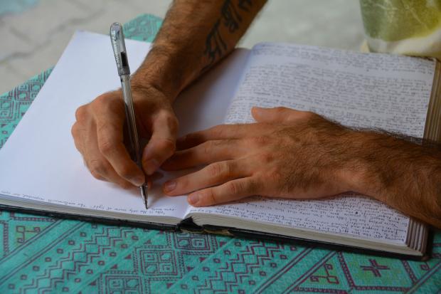 мужчина пишет в дневнике