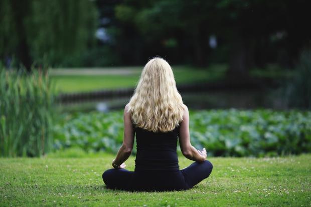 девушка с длинными кудрявыми волосами медитирует