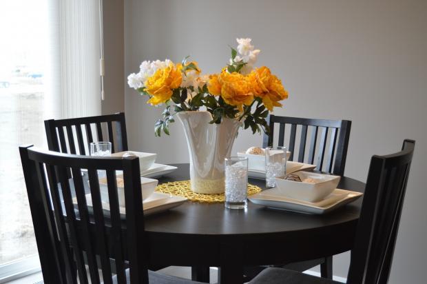 в белой вазе на обеденном столе стоит букет цветов