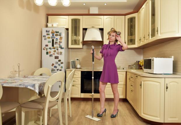 женщина со шваброй в кухне