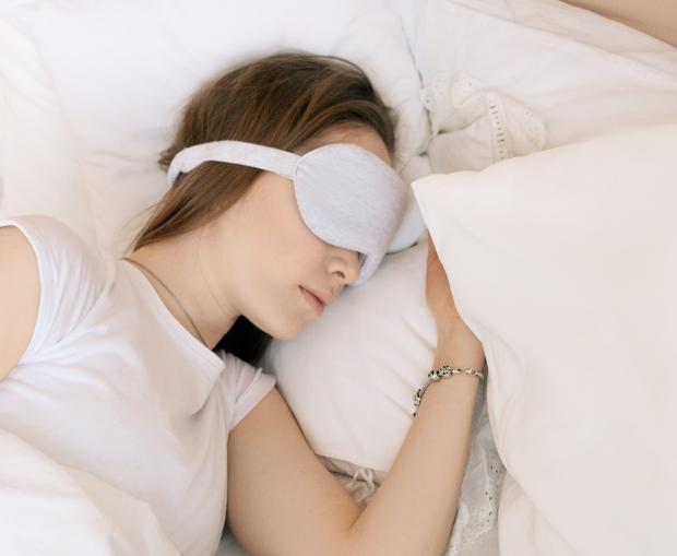 спящая в маске для глаз девушка