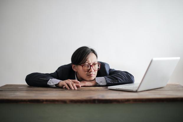 мужчина в очках лежит на столе перед ноутбуком