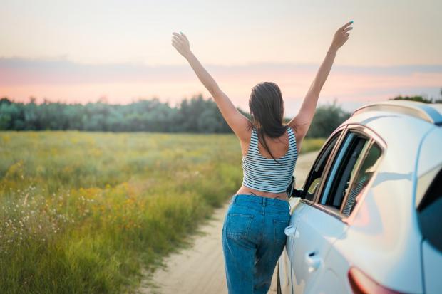 девушка в джинсах и сайке возле автомобиля