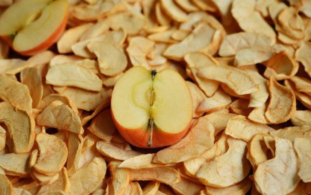 на сушеных яблоках лежит половинка свежего