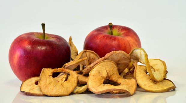 лежат два красных яблока и сухофрукты