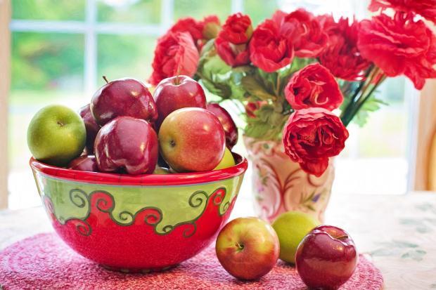 тарелка с красными яблоками стоит на столе рядом с букетом ярких пионов