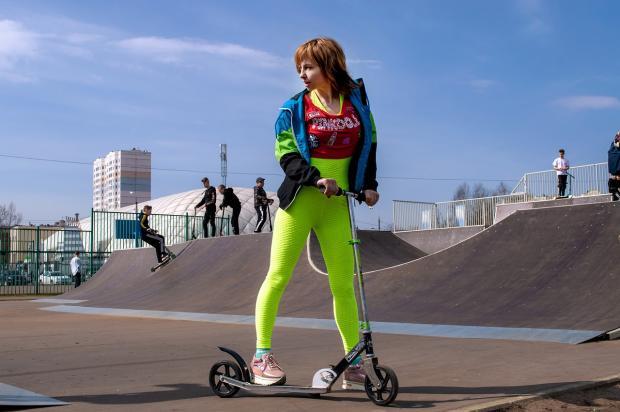 девушка в зеленых леггинсах на скутере