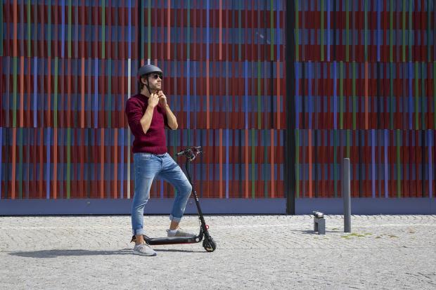 мужчина на электросамокате в синих джинсах надевает шлем